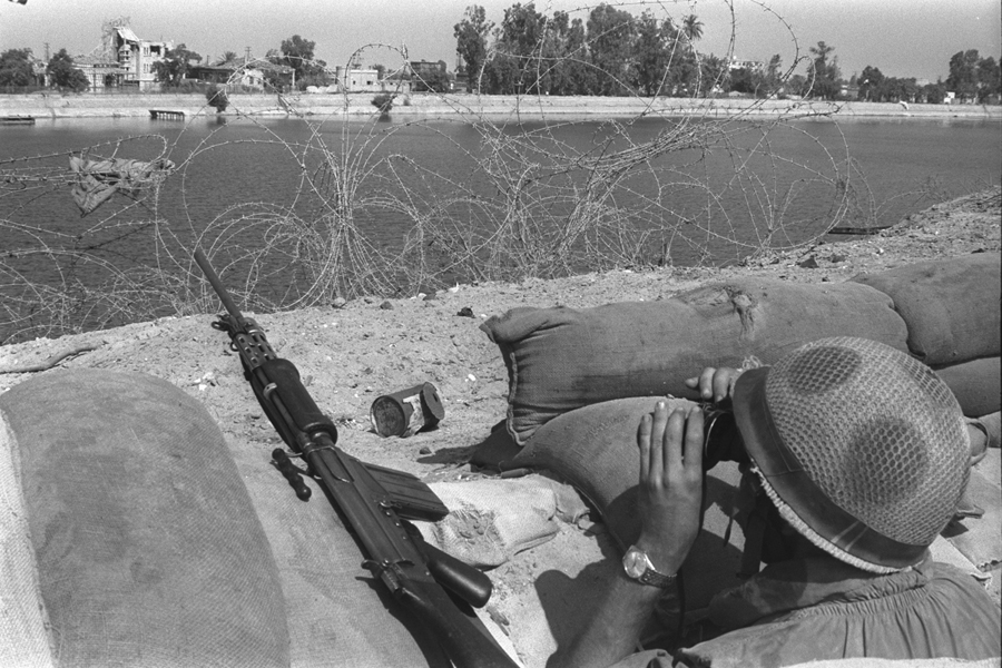 An Israeli soldier looks across the Suez Canal during the War of Attrition, August 1970. (Photo by Moshe Milner, courtesy of Government Press Office, Israel.)